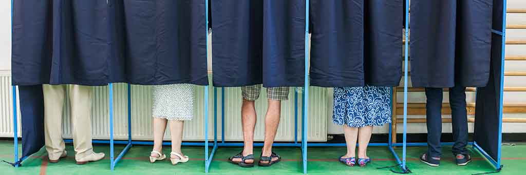 Stock image of people voting in booths.