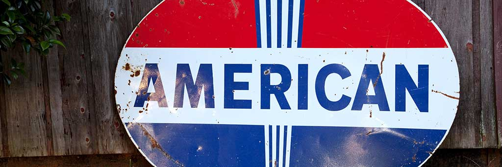 """Stock image of a metal sign with the word """"American"""" on it."""