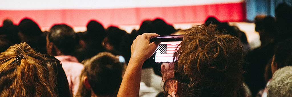 Stock image of a woman capturing video on a mobile device at a political rally.