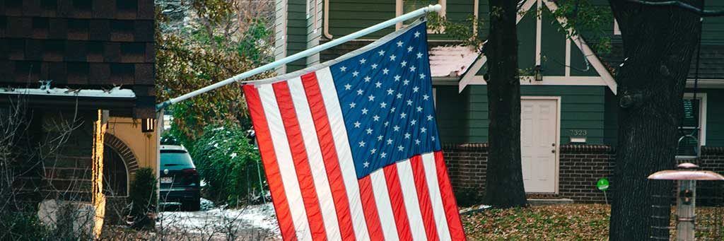 Stock image of an American flag hanging in a yard.