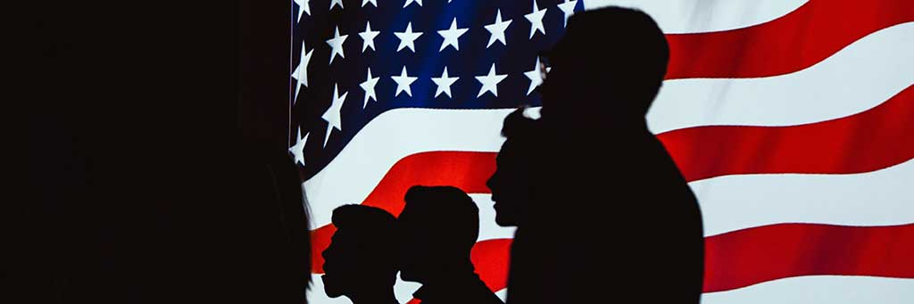 Stock image of a group silhouette in front of an American flag.