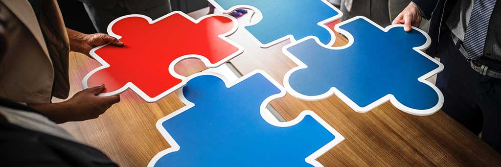 Stock image of a group putting oversized puzzle pieces together.